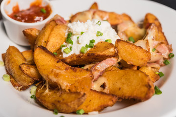Potato wedges with bacon and white cream