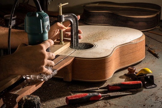 Luthier cutting a channel to place the truss rod in the guitar n
