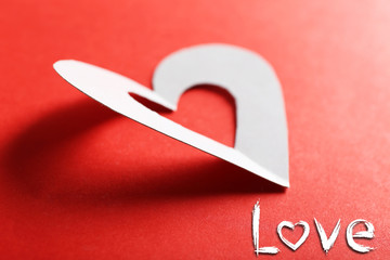 Cut out white paper hearts on red background