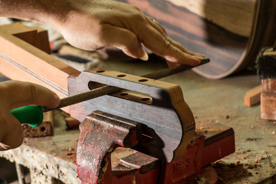 Luthier making a peghead of classical guitar