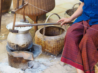 Boiling cocoon silkworm in a pot to prepare silk thread