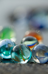 Marbles on the sidewalk close up. Diversity of colors. Blurry in the back.
