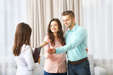 Estate agent giving keys to  couple, on light background
