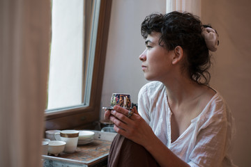 Asian woman looking out the window and drinking tea