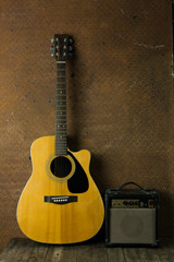 Acoustic guitar and amplifier resting against old steel backgrou