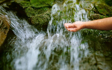 Man's hand reaching to a water spring