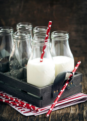 Crate of milk bottles with drinking straws in rustic style
