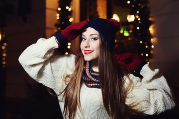 Night street portrait of smiling  beautiful young woman. Model looking at camera. Lady wearing classic winter knitted clothes. Festive garland lights. Close up.
