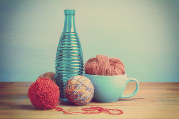 yarn for knitting with a Cup and bottle on wooden table on blue background,photo in the filter