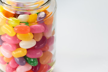 Jelly beans in glass jar on white background