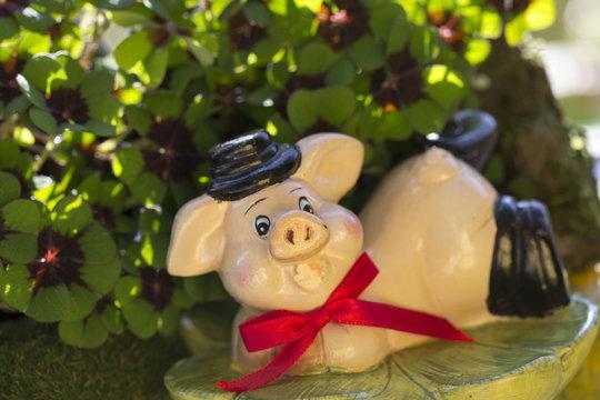 Glücksschwein mit roter Schleife im Klee liegend