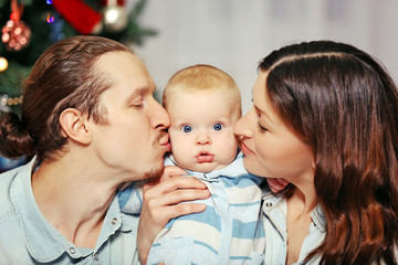 Parents kisses theirs baby in the decorated Christmas room
