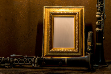 Still life of picture frame on wooden table with clarinet