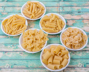 Various dried pasta variety and shapes in white bowl over wooden background