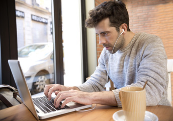 Young man listens to and write on computer with cup of coffee