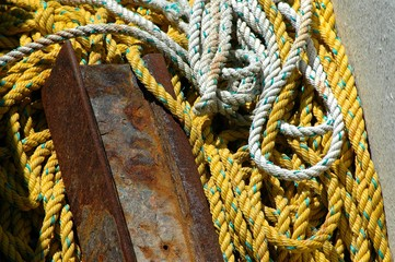 White and yellow rope and a piece of rusty metal; Coils of white and yellow rope lying with a piece of rust metal
