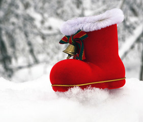 Christmas Santa boot on snowy forest background.
