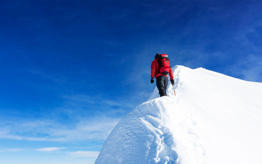 Foto op Aluminium Alpinisme Mountaineer reach the summit of a snowy peak. Concepts: determination, courage, effort, self-realization. Clear sky, sunny day, winter season. Large copy-space on the left. European Alps, Europe.