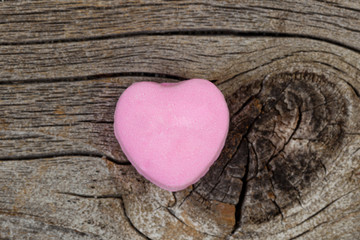 Happy Valentines day with single pink heart shaped candy on wood