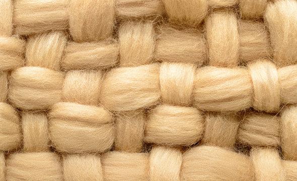 Interweaving beige wool closeup. Background made of wool for felting