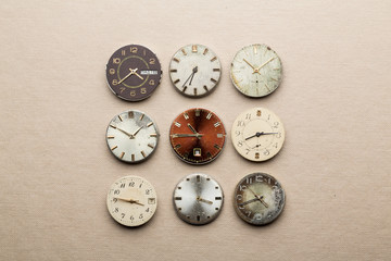 Nine old clock dials showing different time