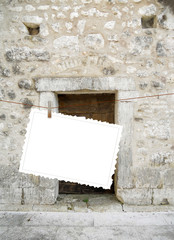 Close-up of one hanged postcard on ancient wall and door background