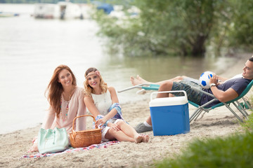 Two beautiful young women having a picnic on the beach with their friends