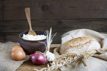 Rustic natural dairy products. Rustic natural dairy products cottage cheese and bread, eggs, onions and garlic of wheat on the old wooden background.