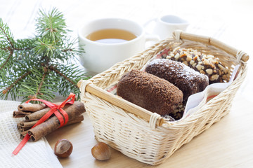 Fresh hot green tea in white cup with chocolate cakes in basket.