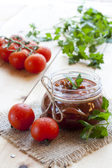 Tomato sauce (jam) in glass jar with parsley and fresh tomatos on dark wooden table, selective focus.