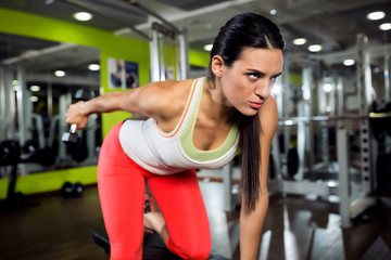 Strong fitness angry girl doing training with weight