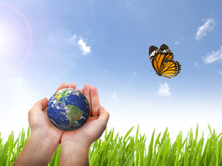 Earth planet and butterfly in female hand on blue sky