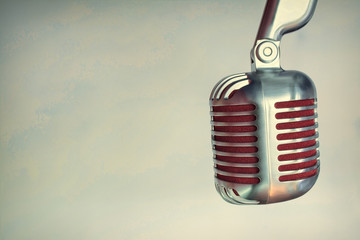 silver vintage microphone with red membrane сlose up on a grey vintage background