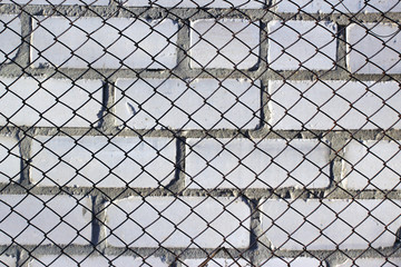 Chain link fence on white brick wall