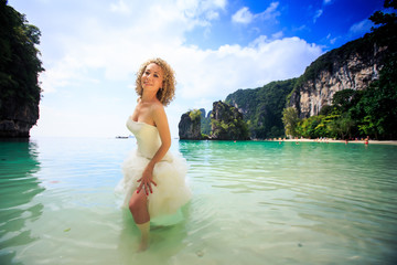 blonde bride in fluffy dress stands in shallow azure sea
