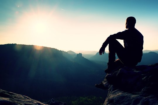 Tourist take a rest. Handsome young man sitting on the rock and enjoying view into misty rocky mountains.