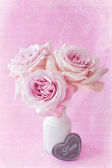Beautiful fresh pink roses on a pink background. Vintage style ,grunge paper background.