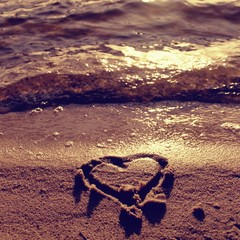 Lovely small heart sketched in salt  sand at beach. Evening warm colors of sunset mirror in water level.