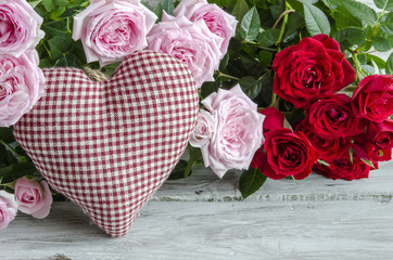 Checked handmade heart against of red and pink roses