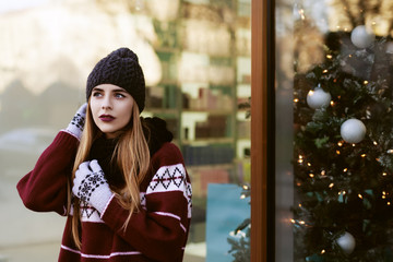 Street portrait of young beautiful woman with long blond hair wearing stylish winter clothes. Model looking aside. Female fashion concept