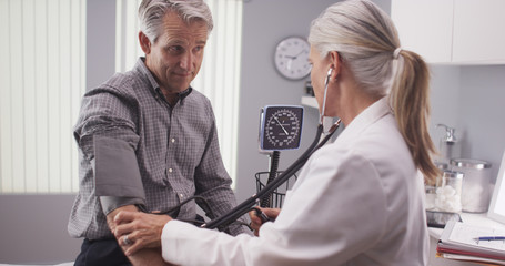 Professional doctor measuring senior man's blood pressure