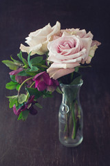 Still life with a fresh roses in a vintage jug on a dark brown wooden background .