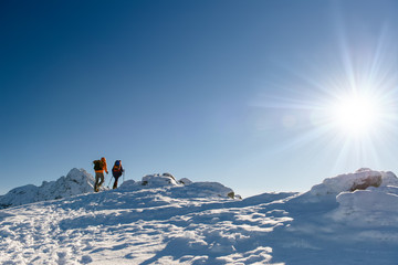 Group hikers in winter mountains, beautiful landscape and blue s
