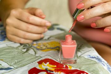Woman applying pink nail polish