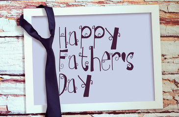"""Happy fathers day"" sign on board and tie hanged on wooden frame."