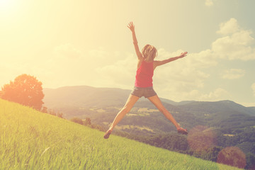 Girl jumping and feeling free in the nature.