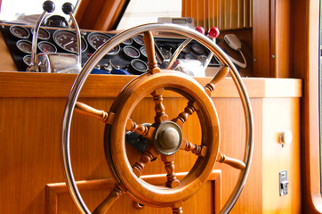 Wooden and metal steering wheel on the interior of a large yacht boat with gauges, engine throttle accelerators and vhf radio in the background