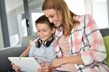Mother with young boy using digital tablet