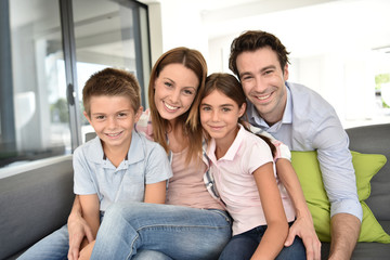 Portrait of happy family sitting in sofa