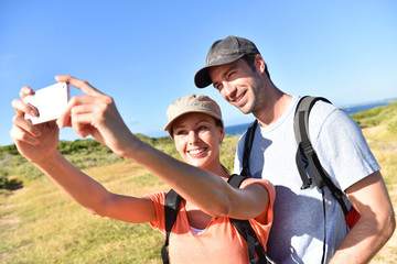 Couple on a trekking day taking picture with smartphone